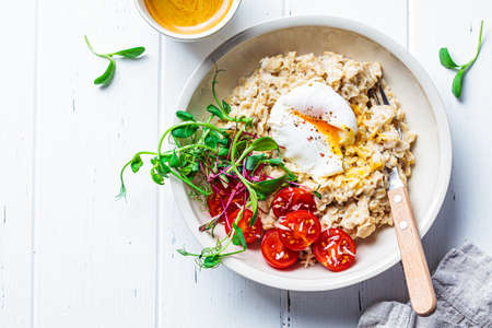 Savory oatmeal with poached egg, tomatoes, cheese and sprouts in a white bowl. Healthy breakfast concept. Imagens