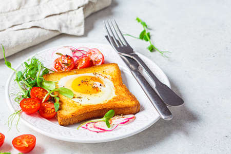 Fried egg in bread toast with tomatoes, radishes and sprouts on a white plate, gray background. Healthy breakfast concept.