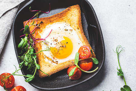 Fried egg in toast bread with tomatoes and sprouts in a black frying pan.