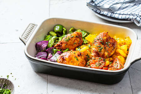 Baked chicken with pepper, tomato and onion in oven dish, gray background. Comfort food concept.