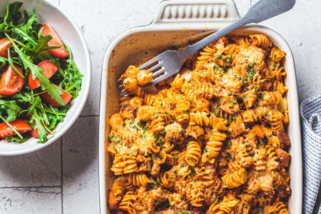 Baked pasta with chicken and cheese in the oven dish, gray background. Italian cuisine concept.