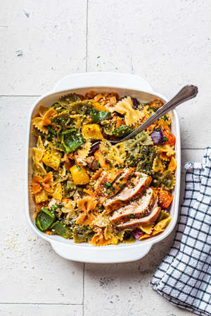 Farfalle pasta with baked vegetables and chicken in a white dish, gray background.