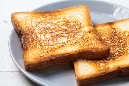 Toast with butter and apricot jam on a gray plate. Breakfast food concept. Imagens