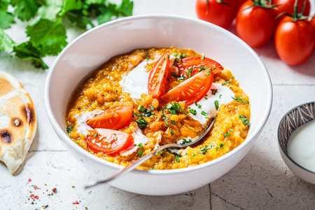 Vegan lentil soup with cilantro and tomatoes. Dal soup with tomatoes. Indian cuisine concept.