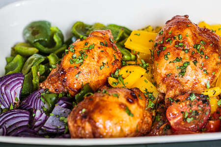 Baked chicken with vegetables in the oven dish, gray background. Comfort food concept.