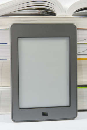 Electronic book reader with blank screen and pile of books  photo