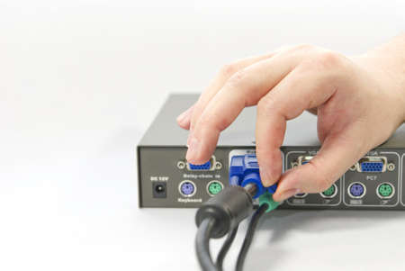 whitem: KVM  keyboard, video and mouse  switch and a human hand with an VGA  Video Graphics Array  connector on white background