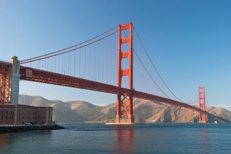 バック グラウンドで美しい紺碧の海と、日没時に San Francisco のゴールデン ゲート ブリッジ