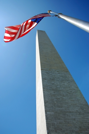 Washington Monument in Washington DC with flapping american flag on a flagpole photo