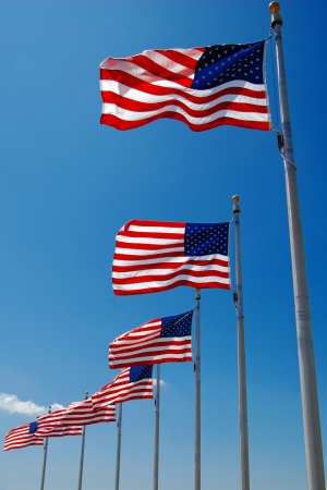 US flags flapping in wind at Washington Monument, Washington DC photo