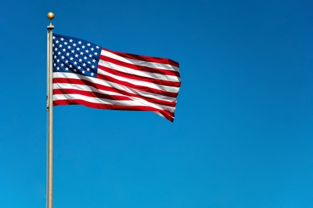 US American flag waving in the wind with beautiful blue sky in background