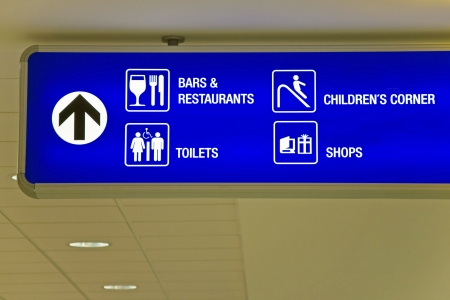 arrival departure board: Detailed view of blue airport sign showing directions