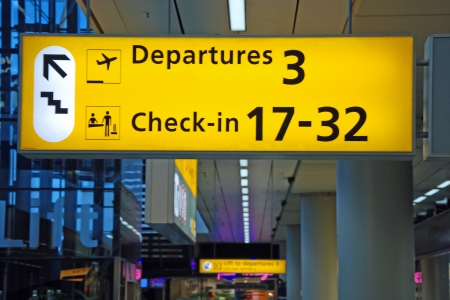 ゲートへの方向を示す黄色の空港発車標の詳細ビュー 写真素材