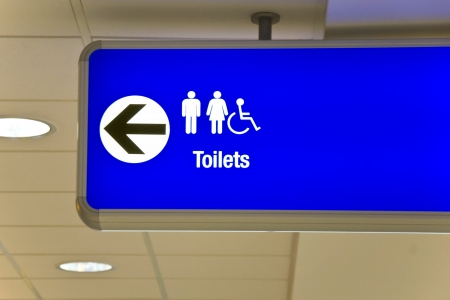 Detailed view of blue airport sign showing directions