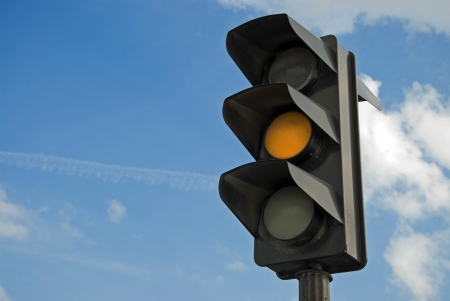 stop and go light: Amber color on the traffic light with a beautiful blue sky in background