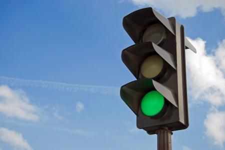 señal transito: El color verde en el semáforo con un hermoso cielo azul de fondo