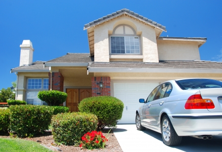 droomhuis: Nieuwe Amerikaanse droom huis met een mooie blauwe hemel in achtergrond en gloednieuwe auto buiten geparkeerd. Redactioneel