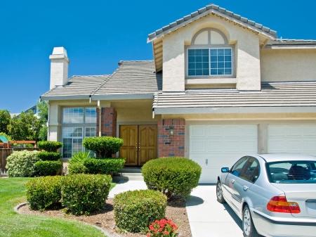soñar carro: Nuevo hogar del sueño americano con un hermoso cielo azul en el fondo y el coche nuevo aparcado fuera. Editorial