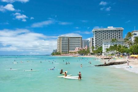 OAHU, HI - SEPTEMBER 19, 2011 - Tourist sunbathing and surfing on Waikiki beach September 19, 2011 in Oahu. Waikiki beach is beachfront neighborhood of Honolulu, best known for white sand and surfing