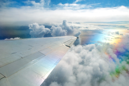 Wing of airplane flying above clouds in the sky and with a view of the ocean in background photo
