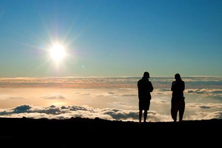 Tourist silhouette watching sunset on the top of  Haleakala volcano on Maui Hawaii photo