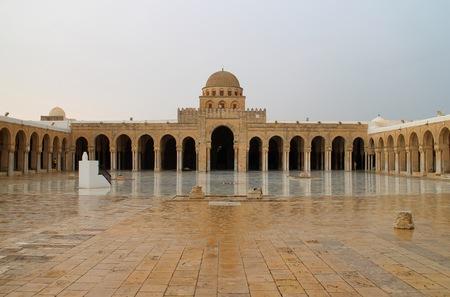 kairouan: Courtyard of great old historic mosque from brown stones. Tile floor. Wide shot. Tunisia - Kairouan