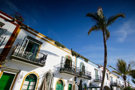 spanish houses: Spanish style colorful houses with balconies and palms around in romantic historic alley. Spain - Gran Canaria - Puerto de Mog�n Stock Photo