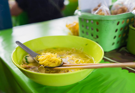yollow asina style noodle call ba mee with meat ball on spoon and chopstick on green resterant table dress with blurred garnish Stock Photo