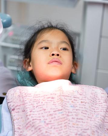 niña niño se acuesta en la cama del dentista listo para comprobar los dientes mirar un poco susto