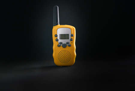 yellow portable radio communition or walkie-talkie on isolated black background