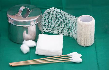 gauze,stainless jar,net roll bandage ,swab,cotton wool on green background
