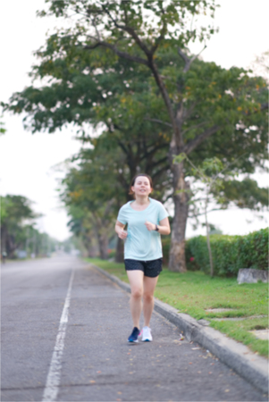 Blur photo of Asian runner is running along traffic street way in the morning Stock Photo