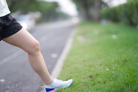 beautiful sport girl legs stand on wayside grass in morning before run with running shoe