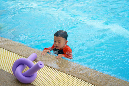 Boy stare at noodle foam for learn swimming on side of water pool Stock Photo