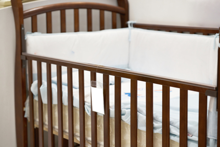 Empty crib with pillow and price slip label
