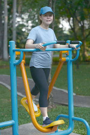 Smile woman exercise on elliptical walk trainer fitness machine in park