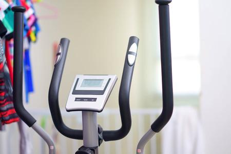 hand holding bars for ellipse fitness training equipment on blur interior home background