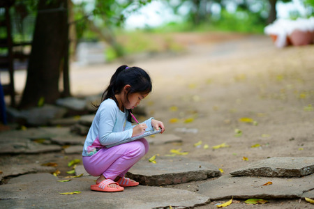niño o niña está escribiendo o dibujando en su bloc de notas o cuaderno de dibujo en el concepto de aprendizaje externo