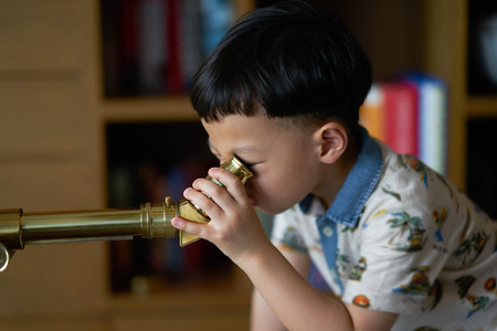 kid or boy concentrates telescope indoors in night time
