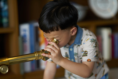 kid or boy concentrates telescope indoors