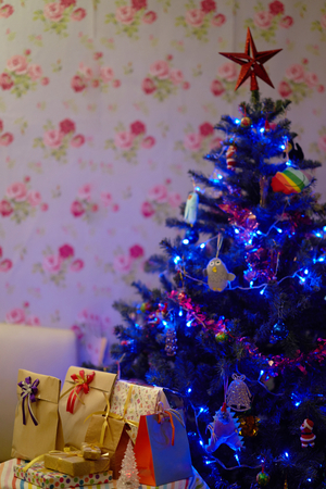 star on top decorated Christmas tree with present boxes inside house Stock Photo