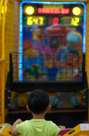 Boy play basket ball game arcade Imagens
