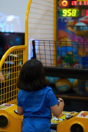 Girl play basket ball shooting in game arcade 版權商用圖片