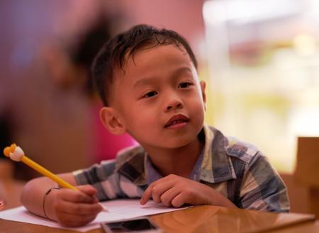 Junge lernt, die Lektion durch Notiz im Buch zu belehren