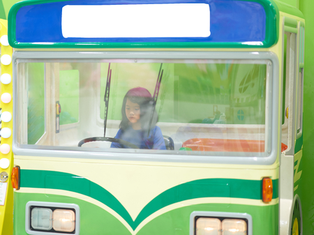young girl plays driving bus