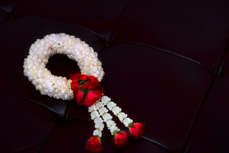 Jasmine and rose garland on leather cover floor background Stock Photo