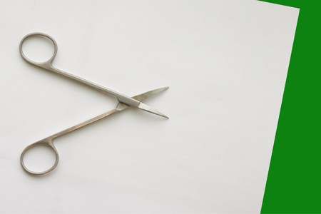 doctor scissors  on white green background with copy space