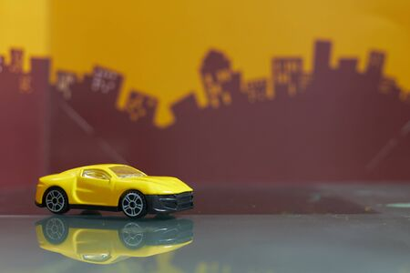 yellow Saloon car toy selective focus on blur city background Фото со стока