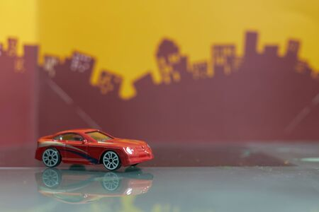 Red  Saloon car toy selective focus on blur city background Фото со стока - 125658269