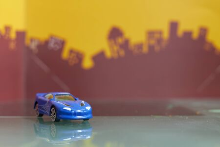 blue Saloon car toy selective focus on blur city background